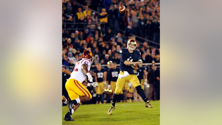 Notre Dame quarterback Tommy Rees throws a pass as Southern California linebacker Devon Dennard closes during the first quarter of a college football game on Saturday, Oct. 19, 2013, in South Bend, Ind. (AP Photo/Joe Raymond)