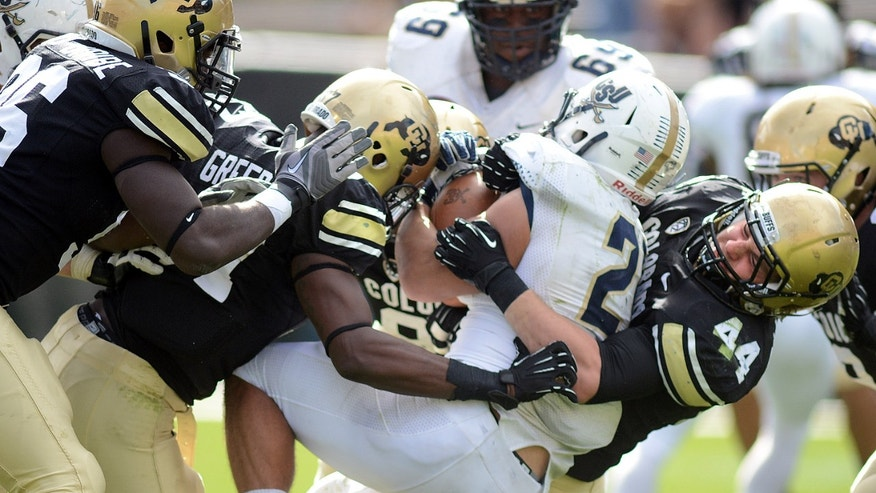 Colorado's Addison Gillam, right, helps bring down Charleston Southern's Christian Reyes during an NCAA college football game Saturday, Oct. 19, 2013, in Boulder, Colo. (AP Photo/Daily Camera, Cliff Grassmick) NO SALES