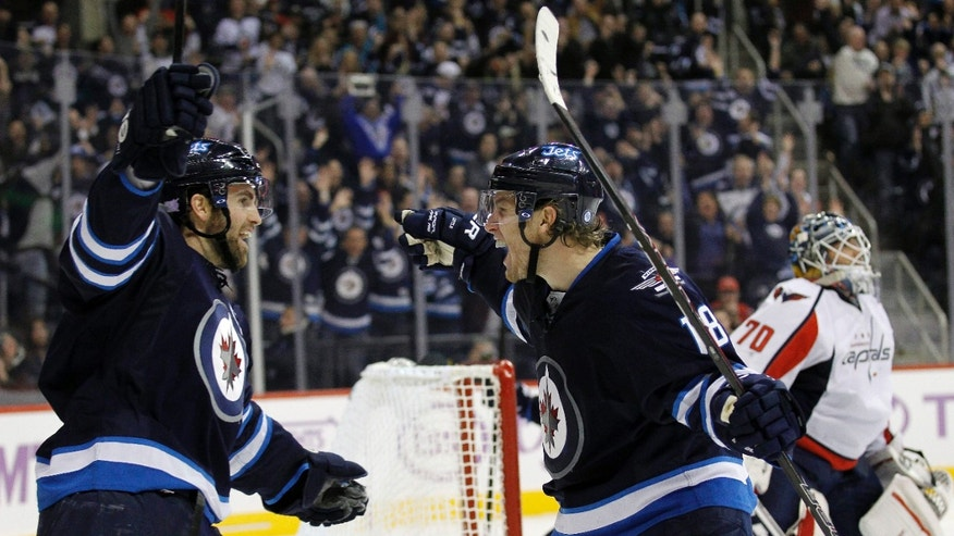 Winnipeg Jets' Andrew Ladd, left, and Bryan Little (18) celebrate after Little scored past Washington Capitals' goaltender Braden Holtby (70) during the second period of an NHL hockey game in Winnipeg, Manitoba, Tuesday, Oct. 22, 2013. (AP Photo/The Canadian Press, Trevor Hagan)