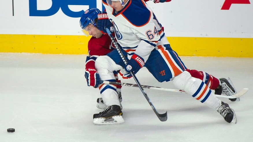 Montreal Canadiens' David Desharnais, left, and Edmonton Oilers' Nail Yakupov chase down the puck during the second period of an NHL hockey game in Montreal, Tuesday, Oct. 22, 2013. (AP Photo/The Canadian Press, Graham Hughes)