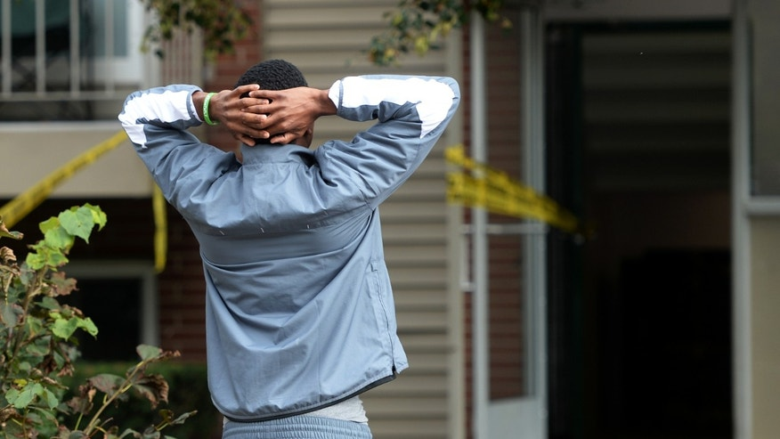 Eastern Michigan football player Donald Scott, takes a moment as he stands in front of the doorway to an apartment building at University Green Apartments,  located in the 700 block of W. Clark in Ypsilanti, Mich., where teammate Demarius Reed was shot to death early on Friday, Oct. 18, 2013. (AP Photo / The Ann Arbor News, Melanie Maxwell)