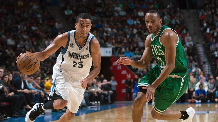 Minnesota Timberwolves' Kevin Martin, left, drives to the net as Boston Celtics' Avery Bradley defends during the third quarter of an NBA preseason basketball game in Montreal, Sunday, Oct. 20, 2013. (AP Photo/The Canadian Press, Graham Hughes)