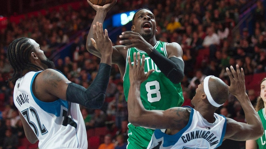 Boston Celtics' Jeff Green, center, takes a shot as Minnesota Timberwolves' Ronny Turiaf, left, and Dante Cunningham defend during the first quarter of an NBA preseason basketball game in Montreal, Sunday, Oct. 20, 2013. (AP Photo/The Canadian Press, Graham Hughes)