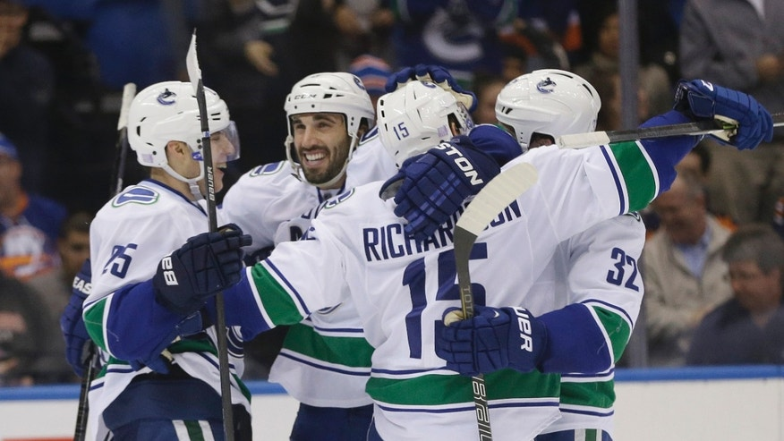 Vancouver Canucks' Jason Garrison smiles as he celebrates with Mike Santorelli (25) and Dale Weise (32) after Brad Richardson (15) scored during the overtime period of an NHL hockey game Tuesday, Oct. 22, 2013 in Uniondale, N.Y. The Canucks won the game 5-4. (AP Photo/Frank Franklin II)