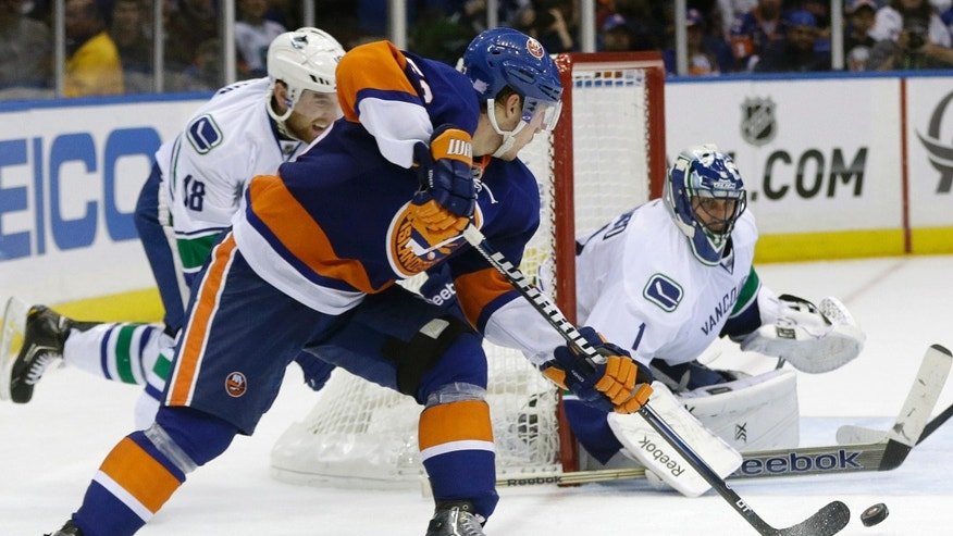 Vancouver Canucks goalie Roberto Luongo (1) stops a shot on the goal by New York Islanders' Casey Cizikas (53) during the second period of an NHL hockey game Tuesday, Oct. 22, 2013 in Uniondale, N.Y. (AP Photo/Frank Franklin II)