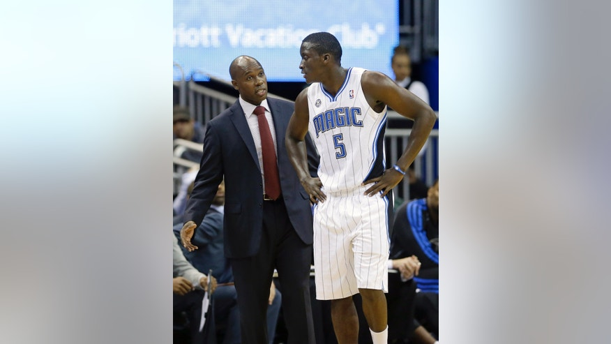 Orlando Magic head coach Jacque Vaughn, left, talks with Victor Oladipo (5) during a time out in the second half of an NBA preseason basketball game against the Memphis Grizzlies in Orlando, Fla., Friday, Oct. 18, 2013. The Memphis Grizzlies won the game 97-91.(AP Photo/John Raoux)