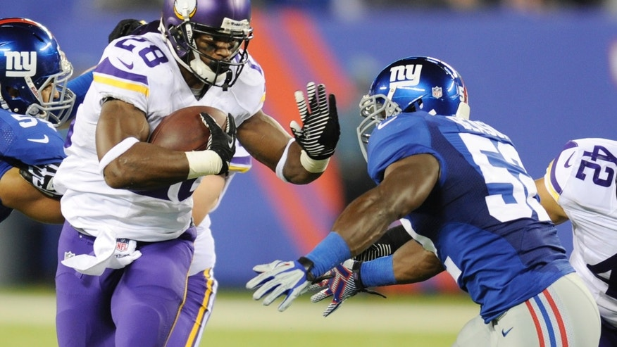 Minnesota Vikings running back Adrian Peterson (28) stiff-arms New York Giants' Jon Beason (52) during the second half of an NFL football game Monday, Oct. 21, 2013 in East Rutherford, N.J. (AP Photo/Bill Kostroun)