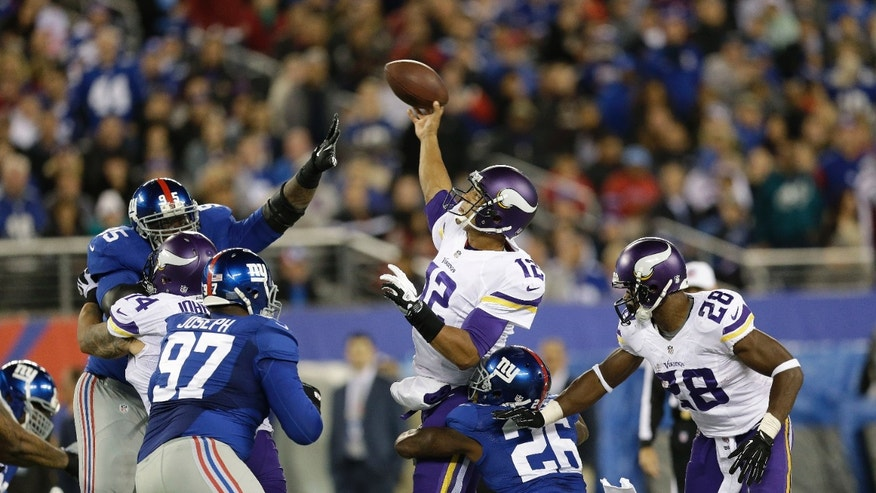 Minnesota Vikings quarterback Josh Freeman (12) throws a pass as he is hit by New York Giants' Antrel Rolle (26) during the second half of an NFL football game Monday, Oct. 21, 2013 in East Rutherford, N.J. (AP Photo/Julio Cortez)
