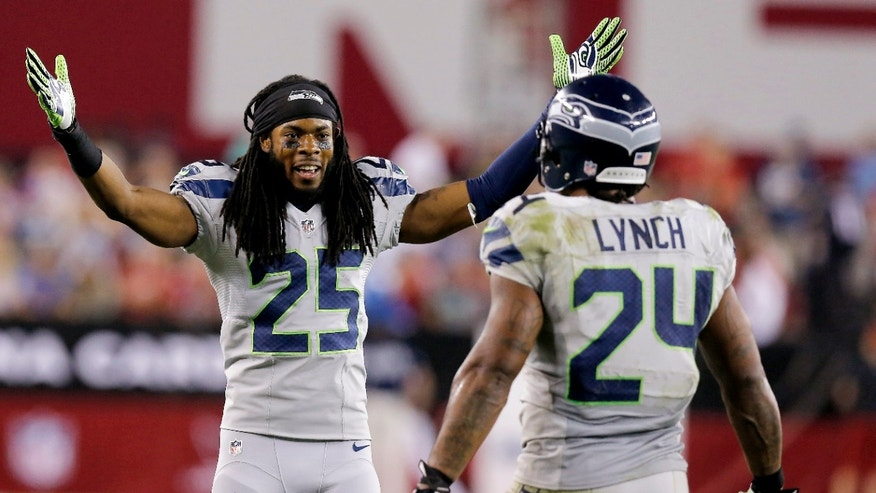 Seattle Seahawks cornerback Richard Sherman (25) greets teammate Marshawn Lynch (24) after Lynch scored a touchdown against the Arizona Cardinals during the second half of an NFL football game, Thursday, Oct. 17, 2013, in Glendale, Ariz. (AP Photo/Ross D. Franklin)