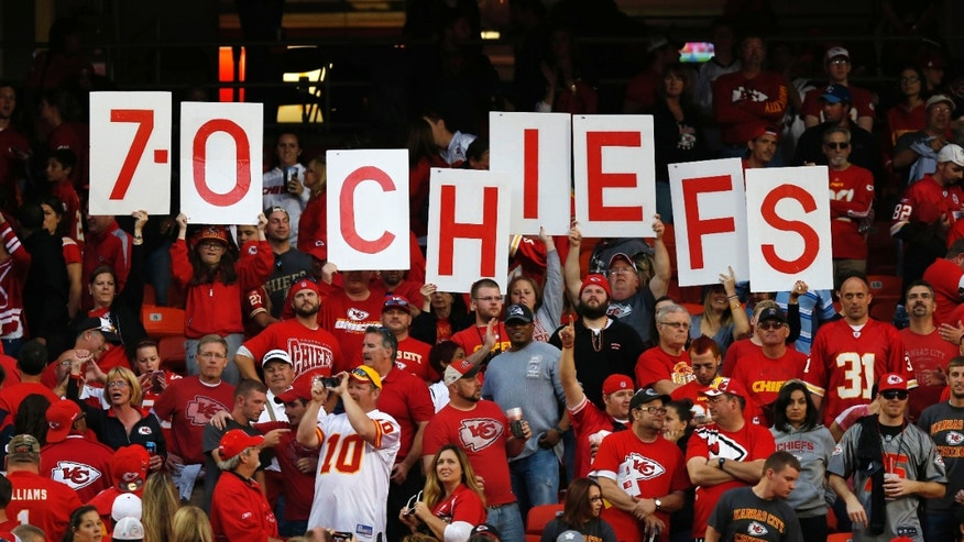 Kansas City Chiefs fans hold up the teams record following an NFL football game against the Houston Texans at Arrowhead Stadium in Kansas City, Mo., Sunday, Oct. 20, 2013. The Chiefs defeated the Texans 17-16. (AP Photo/Ed Zurga)