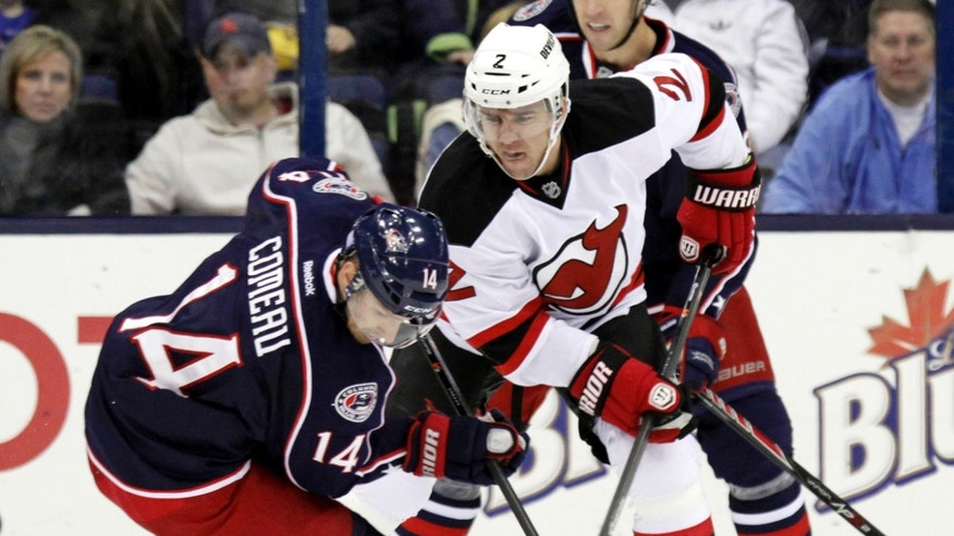 Columbus Blue Jackets' Blake Comeau, left, works for the puck against New Jersey Devils' Marek Zidlicky, of the Czech Republic, in the first period of an NHL hockey game in Columbus, Ohio, Tuesday, Oct. 22, 2013. (AP Photo/Paul Vernon)