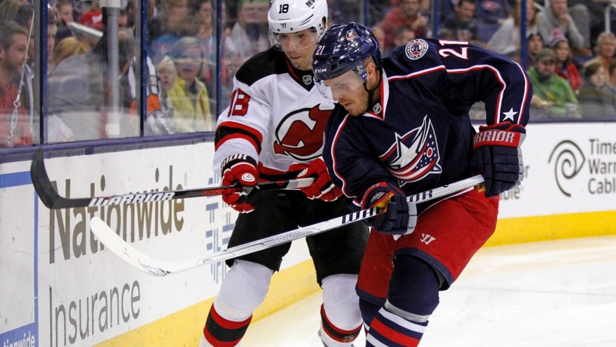 Columbus Blue Jackets' James Wisniewski, right, works for the puck against New Jersey Devils' Steve Bernier in the first period of an NHL hockey game in Columbus, Ohio, Tuesday, Oct. 22, 2013. (AP Photo/Paul Vernon)