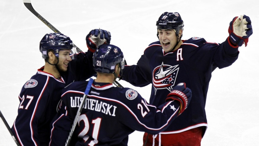 Columbus Blue Jackets' Ryan Murray (27), James Wisniewski (21) and Brandon Dubinsky (17) celebrate after Wisniewski's goal againt New Jersey Devils in the third period of an NHL hockey game in Columbus, Ohio, Tuesday, Oct. 22, 2013. The Blue Jackets won 4-1.  (AP Photo/Paul Vernon)