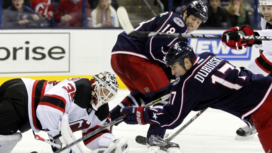 Columbus Blue Jackets' Brandon Dubinsky, right, scores against New Jersey Devils goalie Cory Schneider during the second period of an NHL hockey game in Columbus, Ohio, Tuesday, Oct. 22, 2013. (AP Photo/Paul Vernon)