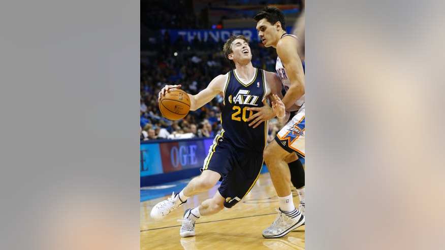 Utah Jazz forward Gordon Hayward (20) is fouled by Oklahoma City Thunder' Steven Adams (12) as he drives to the basket during the third quarter of a preseason NBA basketball game in Oklahoma City, Sunday, Oct. 20, 2013. Oklahoma City won 88-82. (AP Photo/Sue Ogrocki)