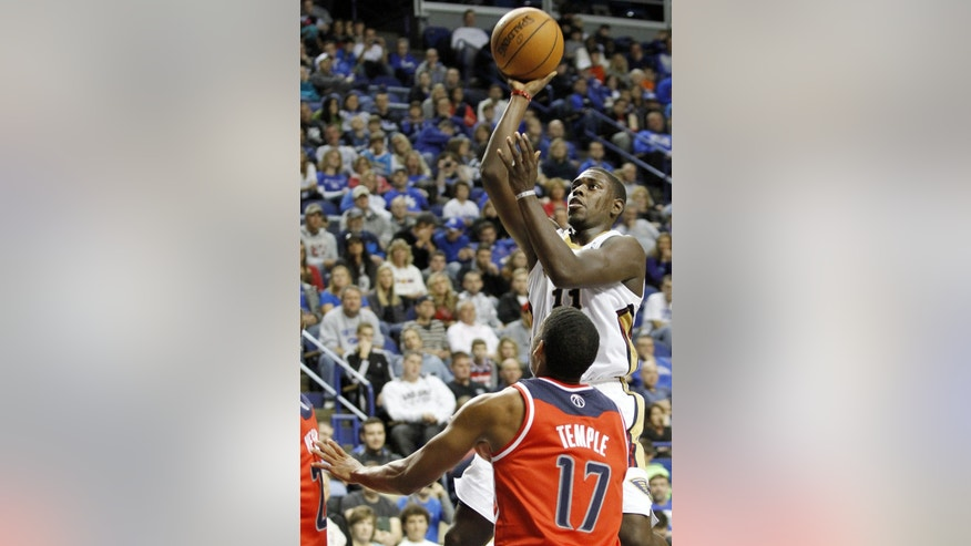New Orleans' Jrue Holiday, right, shoots over Washington's Garrett Temple during the fourth quarter of an NBA basketball exhibition game, Saturday, Oct. 19, 2013, in Lexington, Ky. New Orleans won 93-89. (AP Photo/James Crisp)