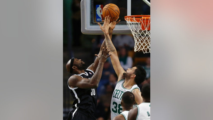 Boston Celtics' Vitor Faverani (38) blocks the shot by Brooklyn Nets' Reggie Evans (30) in the first quarter of a preseason NBA basketball game in Boston, Wednesday, Oct. 23, 2013. (AP Photo/Michael Dwyer)