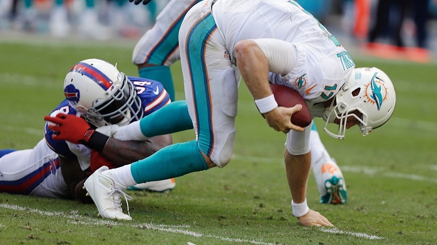 Buffalo Bills defensive end Mario Williams, left, holds onto the Miami Dolphins quarterback Ryan Tannehill's foot during the second half of an NFL football game, Sunday, Oct. 20, 2013, in Miami Gardens, Fla. The Bills won 23-21. (AP Photo/Lynne Sladky)