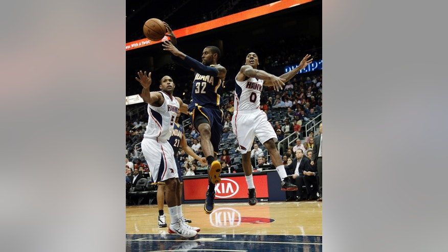 Indiana Pacers point guard C.J. Watson (32) passed the ball as he drives past Atlanta Hawks' Al Horford, left, and Jeff Teague (0) during the first half of a preseason NBA basketball game Tuesday, Oct. 22, 2013, in Atlanta. (AP Photo/John Bazemore)
