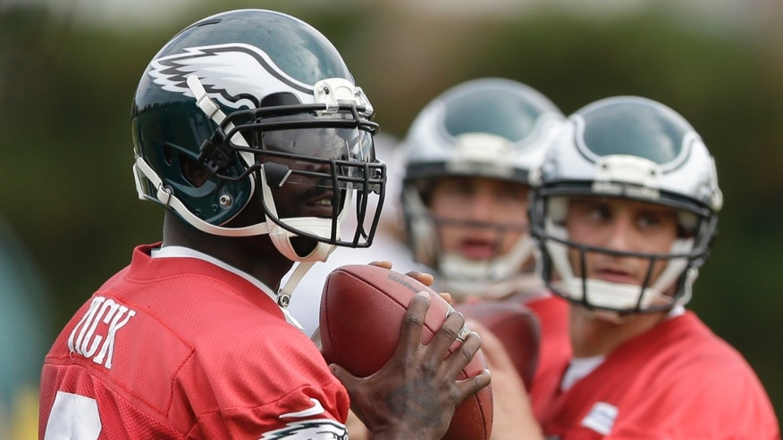 Philadelphia Eagles quarterback Michael Vick, left, G. J. Kinne, right, and Matt Barkley throw passes during practice at the NFL football team's training facility, Tuesday, Oct. 22, 2013, in Philadelphia. (AP Photo/Matt Rourke)