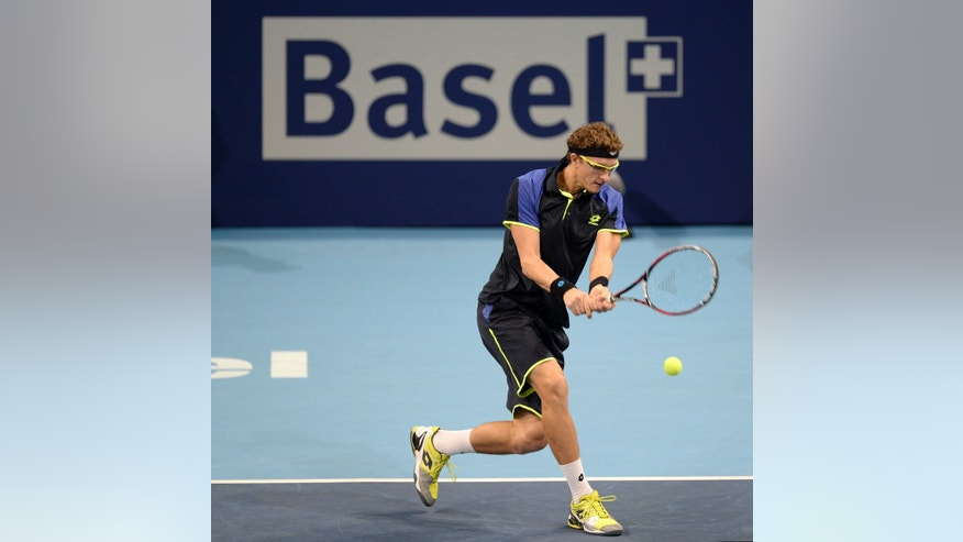 Uzbekistan's Denis Istomin returns a ball to Switzerland's Roger Federer during their second round match at the Swiss Indoors tennis tournament at the St. Jakobshalle in Basel, Switzerland, on Wednesday, Oct. 23, 2013. (AP Photo/Keystone,Georgios Kefalas)