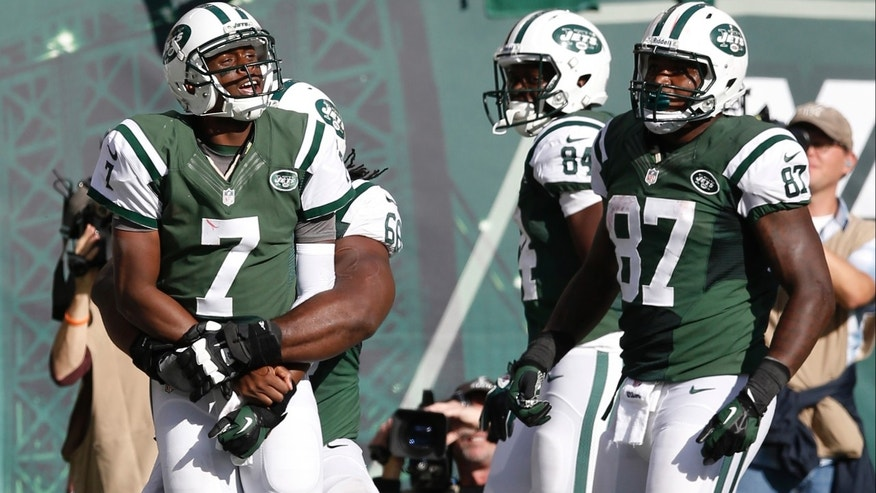 New York Jets quarterback Geno Smith (7) celebrates with teammates after scoring a touchdown during the second half of an NFL football game against the New England Patriots on Sunday, Oct. 20, 2013, in East Rutherford, N.J.  (AP Photo/Kathy Willens)