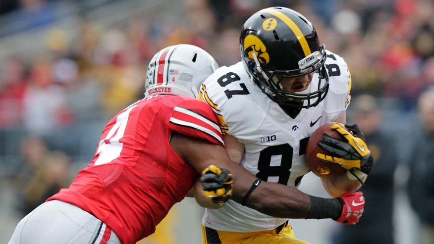 Iowa Tight End Jake Duzey, right, tries to get past Ohio State defensive back C.J. Barnett during the first quarter of an NCAA college football game Saturday, Oct. 19, 2013, in Columbus, Ohio. (AP Photo/Jay LaPrete)