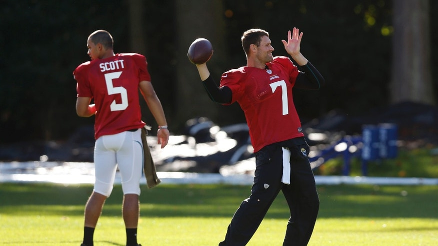 Jacksonville Jaguars' quarterback Chad Henne, right, throws a ball during their football practice at the Pennyhill Park Hotel and Spa in Bagshot, England, Wednesday, Oct. 23, 2013. The Jaguars face the San Francisco 49ers on Sunday in a NFL football game at Wembley Stadium in London. (AP Photo/Sang Tan)