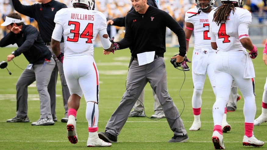 FILE - In this Oct. 19, 2013, file photo, Texas Tech coach Kliff Kingsbury celebrates with Kenny Williams (34) following a touchdown run in the fourth quarter of an NCAA college football game against West Virginia in Morgantown, W.Va. Texas Tech players and coaches say Kingsbury's confidence, drive and energy are behind the No. 10 Red Raiders' success this season. (AP Photo/Christopher Jackson, File)