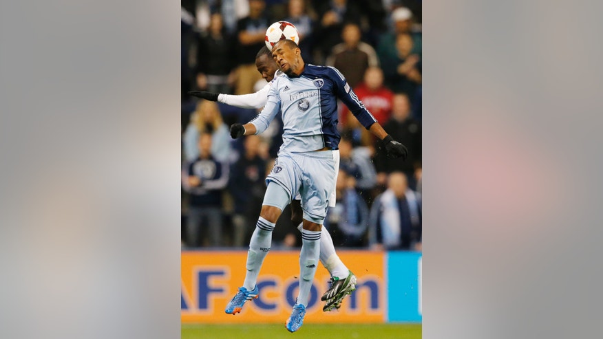 CD Olimpia's Henry Bermudez, back, and Sporting Kansas City's Teal Bunbury (9) head the ball during the first half of a CONCACAF Champions League soccer match in Kansas City, Kan., Wednesday, Oct. 23, 2013. (AP Photo/Orlin Wagner)