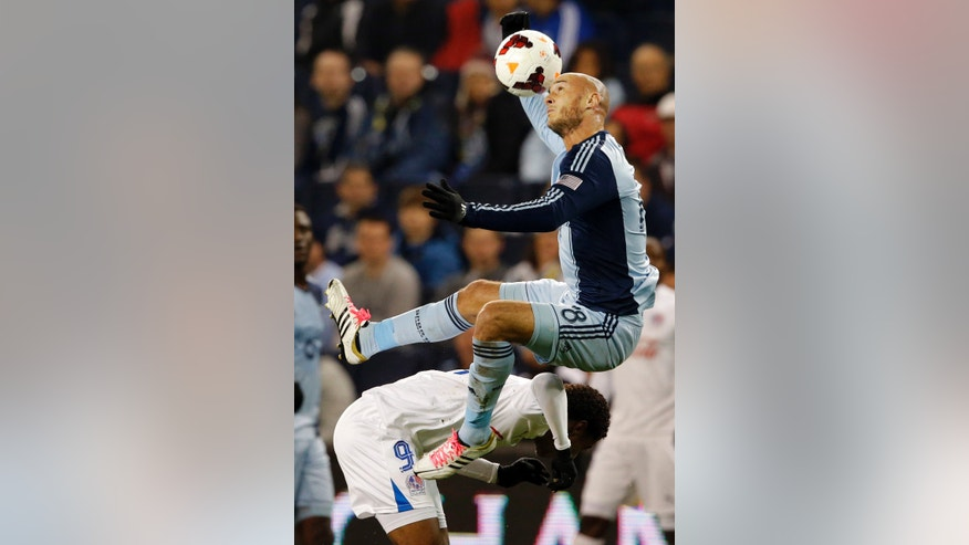 Sporting Kansas City's Aurelien Collin (78) heads the ball over CD Olimpia's Antony Lozano (9) during the first half of a CONCACAF Champions League soccer match in Kansas City, Kan., Wednesday, Oct. 23, 2013. (AP Photo/Orlin Wagner)