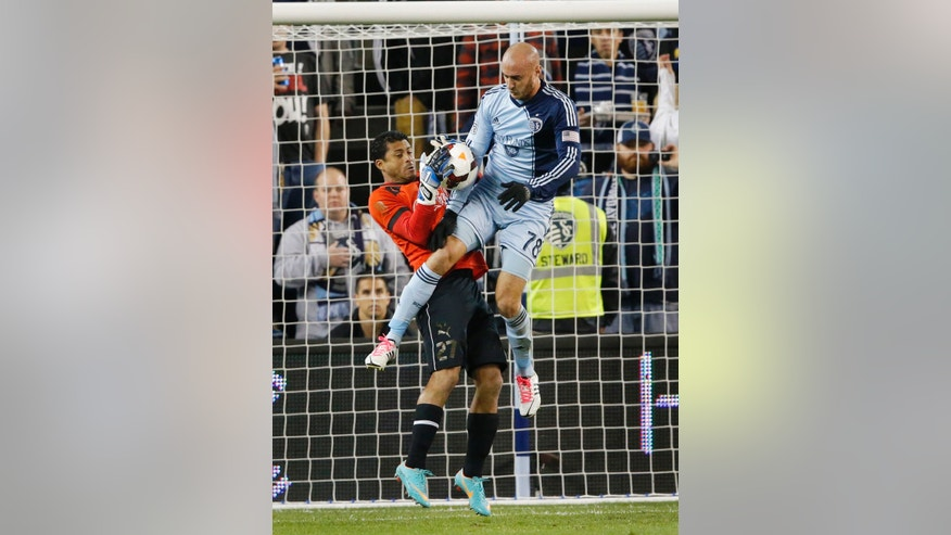 CD Olimpia goalkeeper Noel Valladares (27) battles Sporting Kansas City's Aurelien Collin (78) during the first half of a CONCACAF Champions League soccer match in Kansas City, Kan., Wednesday, Oct. 23, 2013. (AP Photo/Orlin Wagner)