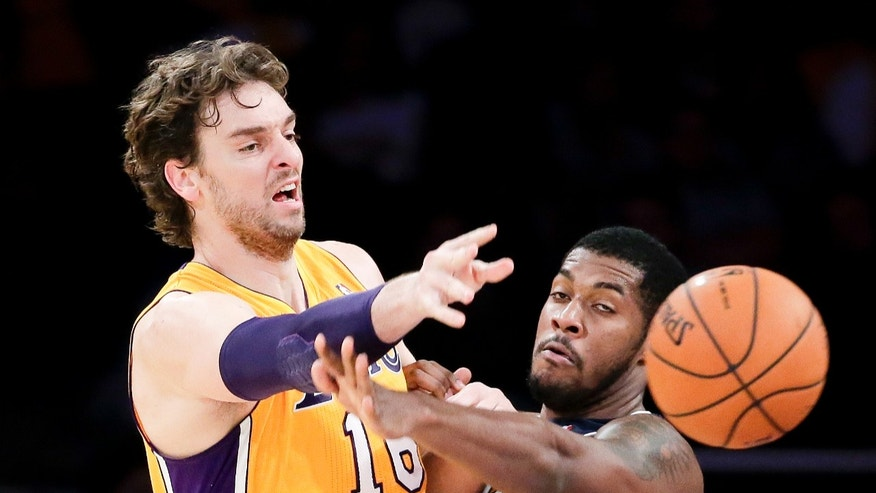 Los Angeles Lakers forward Pau Gasol passes around Utah Jazz forward Derrick Favors during the first half of a preseason NBA basketball game in Los Angeles, Tuesday, Oct. 22, 2013. (AP Photo/Chris Carlson)
