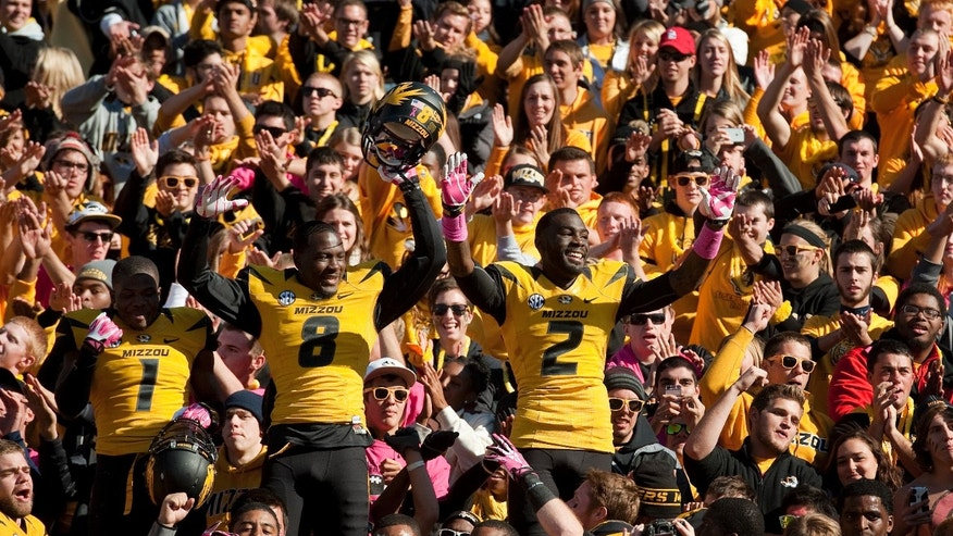 Missouri's L'Damian Washington, right, Darius White, center, and John Gibson, left, celebrate with fans after they defeated Florida 36-17 in an NCAA college football game Saturday, Oct. 19, 2013, in Columbia, Mo. (AP Photo/L.G. Patterson)