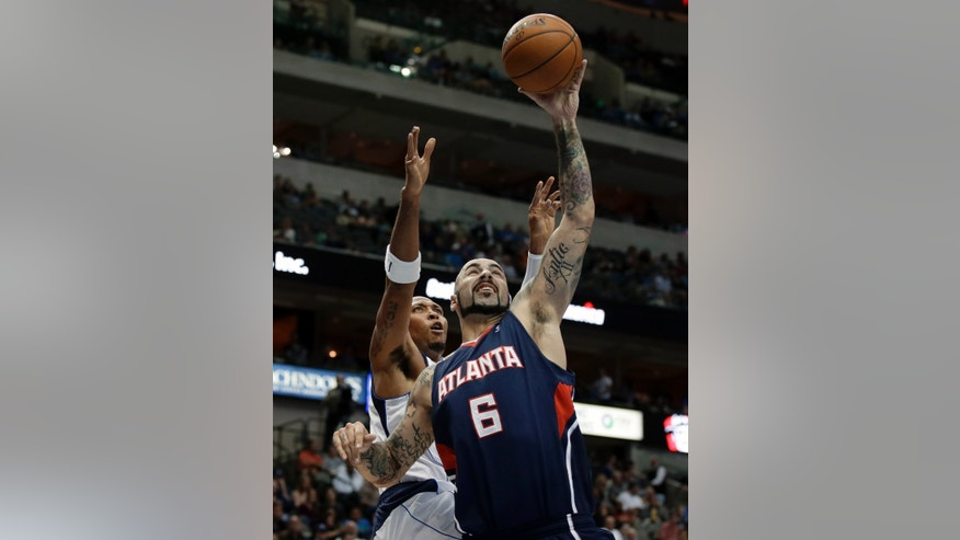 Atlanta Hawks forward Pero Antic, right, of Macedonia comes down with an offensive rebound in front of Dallas Mavericks forward Shawn Marion in the first half of a preseason NBA basketball game Wednesday, Oct. 23, 2013, in Dallas. (AP Photo/Tony Gutierrez)