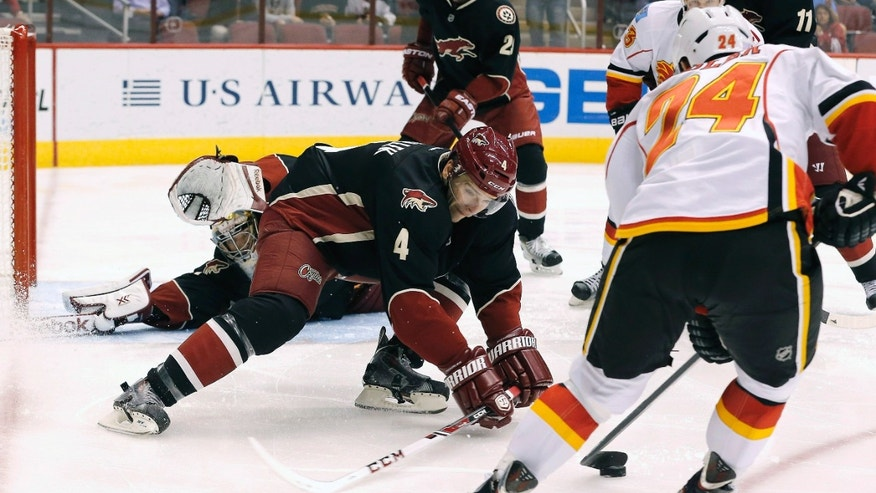Calgary Flames' Jiri Hudler (24), of the Czech Republic, tries to get the puck past Phoenix Coyotes' Zbynek Michalek (4), of the Czech Republic, as he defends the goal in front of a diving Coyotes goalie Mike Smith, left, during the first period of an NHL hockey game on Tuesday Oct. 22, 2013, in Glendale, Ariz. (AP Photo/Ross D. Franklin)