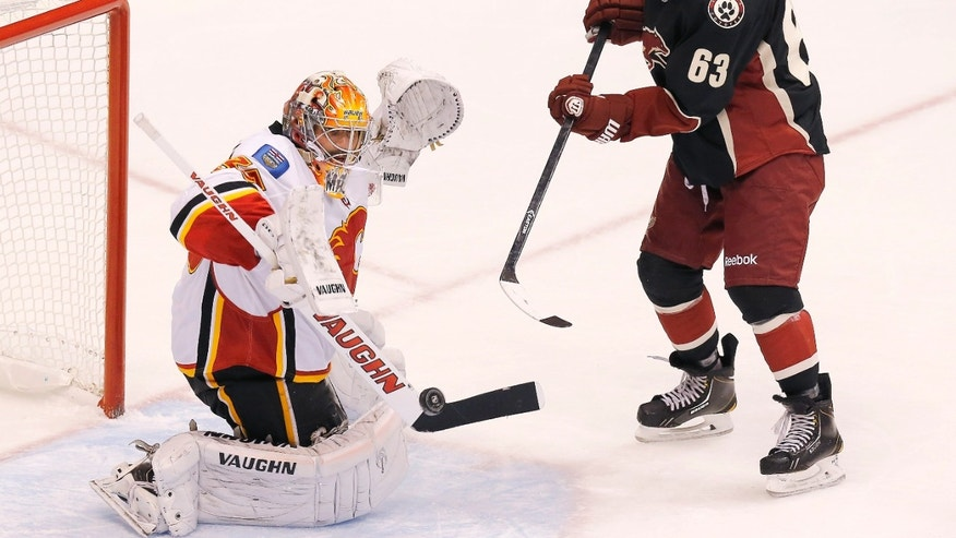 Phoenix Coyotes' Mike Ribeiro (63) flips the puck past Calgary Flames' Joey MacDonald for a goal during the second period of an NHL hockey game on Tuesday Oct. 22, 2013, in Glendale, Ariz. (AP Photo/Ross D. Franklin)