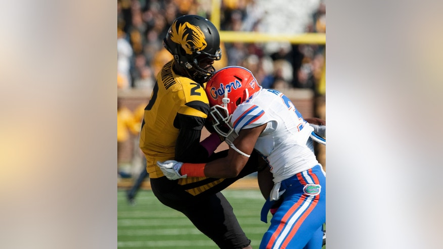 Missouri wide receiver L'Damian Washington, left, is hit by Florida's Cody Riggs, right, after Washington caught a pass on the first play of the first quarter of an NCAA college football game Saturday, Oct. 19, 2013, in Columbia, Mo. Riggs was penalized and ejected on the play for targeting. (AP Photo/L.G. Patterson)