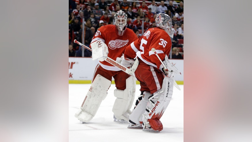 Detroit Red Wings goalie Jonas Gustavsson, left, pats goalie Jimmy Howard after replacing him during the first period of an NHL hockey game against the Ottawa Senators in Detroit, Wednesday, Oct. 23, 2013. (AP Photo/Carlos Osorio)
