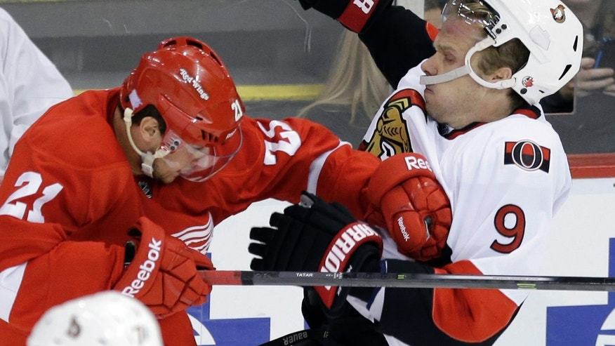 Detroit Red Wings center Tomas Tatar, left, of Slovakia, checks Ottawa Senators left wing Milan Michalek during the second period of an NHL hockey game in Detroit, Wednesday, Oct. 23, 2013. (AP Photo/Carlos Osorio)
