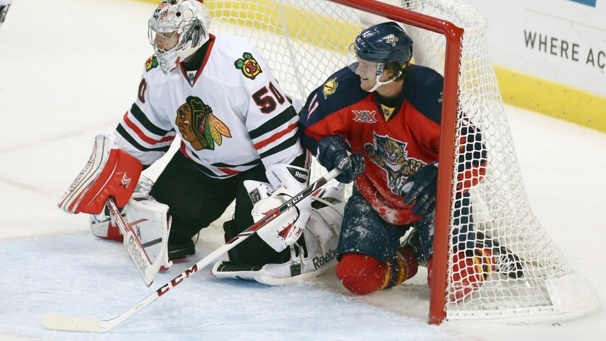 Florida Panthers' Jonathan Hueberdeau (11) slides into the goal and watches game action with Chicago Blackhawks' goalie Corey Crawford (50) during the second period of an NHL hockey game in Sunrise, Fla., Tuesday, Oct. 22, 2013. (AP Photo/J Pat Carter)