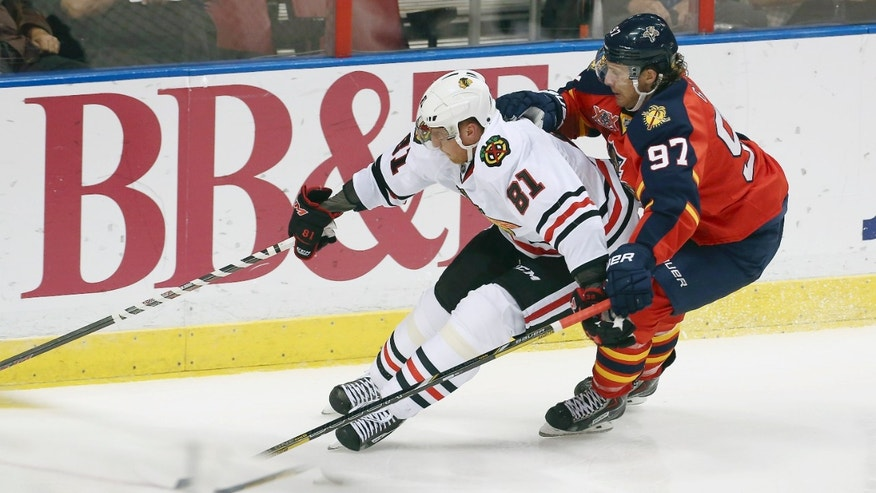Chicago Blackhawks' Marian Hossa (81) and Florida Panthers' Matt Gilroy (97) chase the puck during the second period of an NHL hockey game in Sunrise, Fla., Tuesday, Oct. 22, 2013. (AP Photo/J Pat Carter)