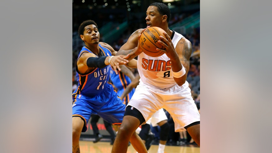 Phoenix Suns' Channing Frye (8) pulls down rebound as Oklahoma Thunder guard Jeremy Lamb defends during the first half of an NBA preseason basketball game, Tuesday, Oct. 22, 2013, in Phoenix. (AP Photo/Matt York)