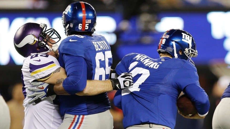 Minnesota Vikings defensive end Jared Allen (69) sacks New York Giants quarterback Eli Manning (10) as tackle Will Beatty (65) attempts to block him during the first half of an NFL football game Monday, Oct. 21, 2013 in East Rutherford, N.J. (AP Photo/Julio Cortez)