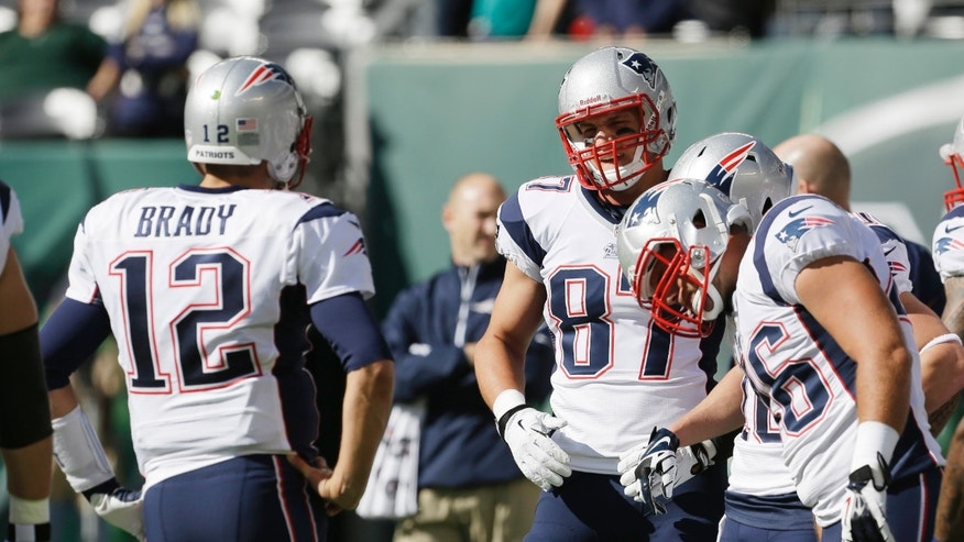 New England Patriots tight end Rob Gronkowski (87) talks to teammate Tom Brady (12) before an NFL football game against the New York Jets Sunday, Oct. 20, 2013 in East Rutherford.  (AP Photo/Seth Wenig)