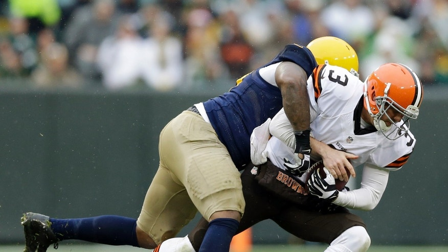 Green Bay Packers' Mike Daniels sacks Cleveland Browns quarterback Brandon Weeden during the first half of an NFL football game Sunday, Oct. 20, 2013, in Green Bay, Wis. (AP Photo/Tom Lynn)