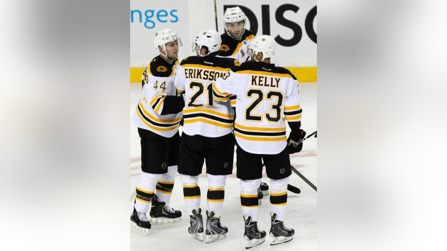 Boston Bruins' Loui Eriksson (21), of Sweden, is helped off the ice by Bruins' Dennis Seidenberg (44), and Chris Kelly (23) after a hit to the head by Buffalo Sabres' John Scott during the third period of an NHL hockey game in Buffalo, N.Y., Wednesday, Oct. 23, 2013.Boston won 5-2. (AP Photo/Gary Wiepert)