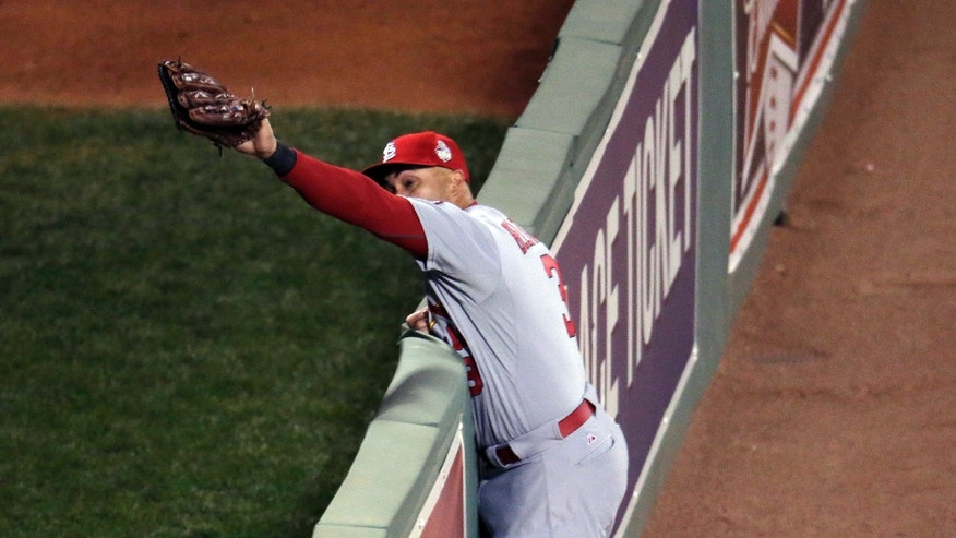St. Louis Cardinals' Carlos Beltran leaps to catch a long fly ball hit by Boston Red Sox's David Ortiz during the second inning of Game 1 of baseball's World Series Wednesday, Oct. 23, 2013, in Boston. (AP Photo/Charlie Riedel)