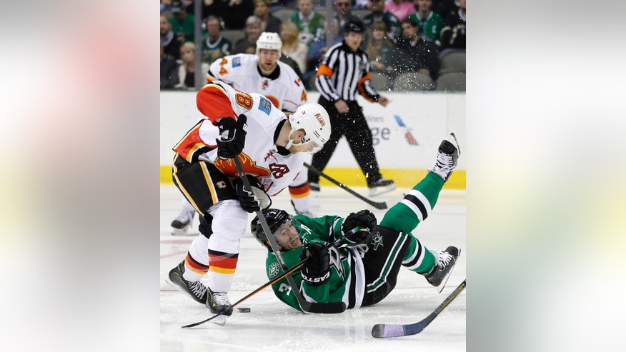 Calgary Flames center Matt Stajan (18) fights with Dallas Stars defenseman Stephane Robidas (3) for control of a loose puck in the first period of an NHL hockey game on Thursday, Oct. 24, 2013, in Dallas. (AP Photo/Tony Gutierrez)