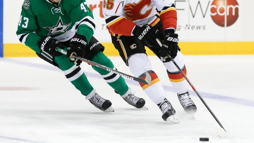 Calgary Flames defenseman Shane O'Brien (55) controls the puck as Dallas Stars' Valeri Nichushkin (43), of Russia, gives chase in the first period of an NHL hockey game, Thursday, Oct. 24, 2013, in Dallas. (AP Photo/Tony Gutierrez)